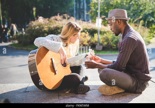 Couple learning to play guitar in park - Stock Image