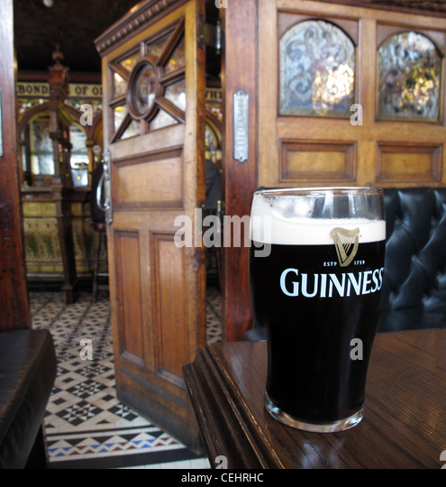 In the crown saloon bar Belfast with a pint of Guiness - Stock Image