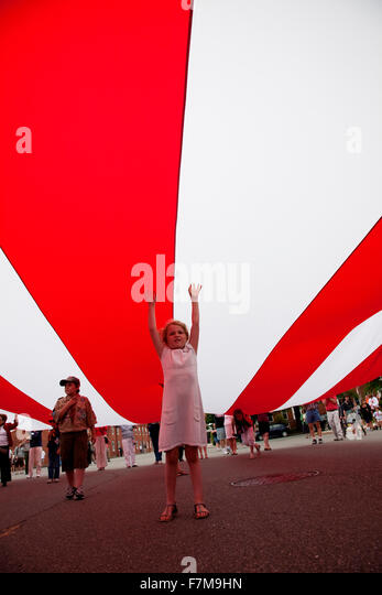 Little girl reaches up underneath US Flag for the Bicentennial of War of 1812 which also feaures Canadian and British - Stock Image