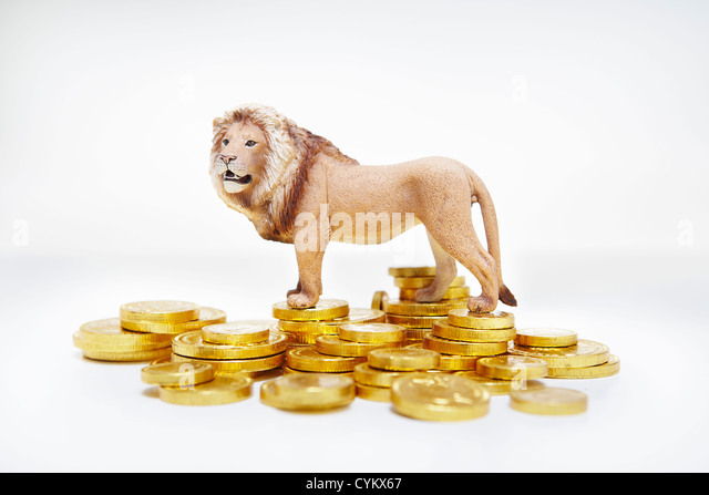 Toy lion on stacks of gold coins - Stock Image