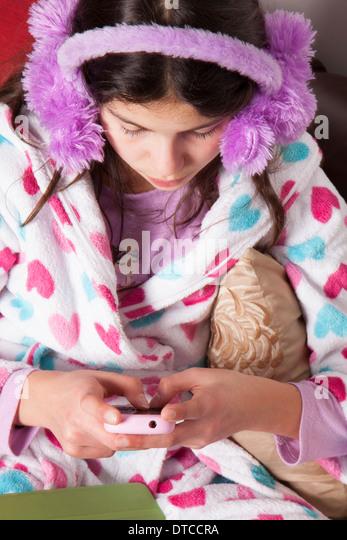 Teenage girl chatting online on her mobile phone - Stock Image