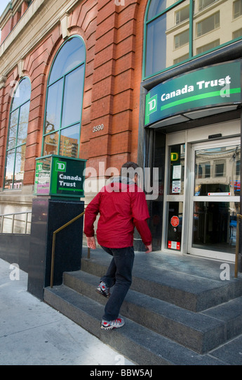 Man entering Canada Trust Bank on Boulevard Saint Laurent Montreal - Stock Image