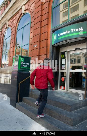 Man entering Canada Trust Bank on Boulevard Saint Laurent Montreal - Stock Image