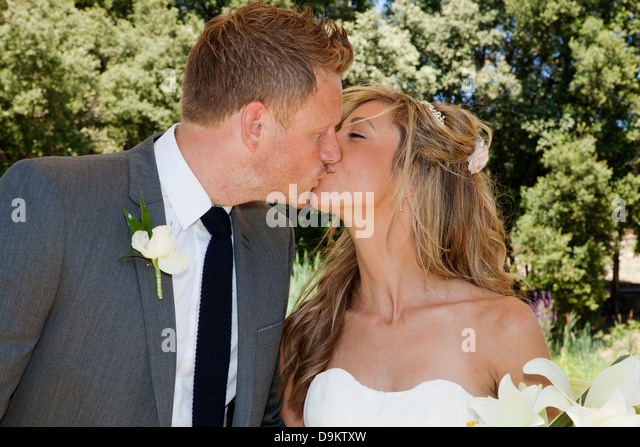 Mid adult bride and groom kissing on wedding day - Stock Image