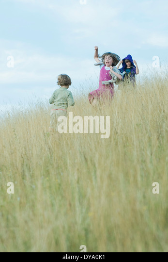 Children playing in tall grass on hillside - Stock Image