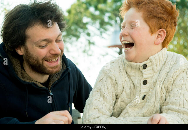 Father and son laughing together outdoors - Stock Image