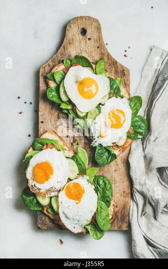 Healthy breakfast sandwiches on rustic wooden board, top view - Stock Image
