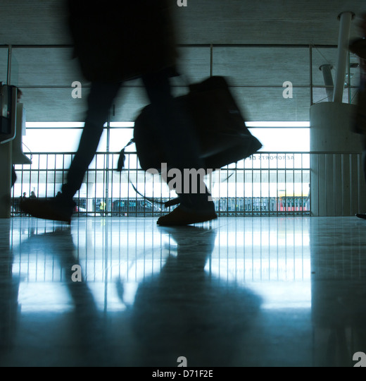 abstract airport and silhouette of walking person with luggage - Stock Image