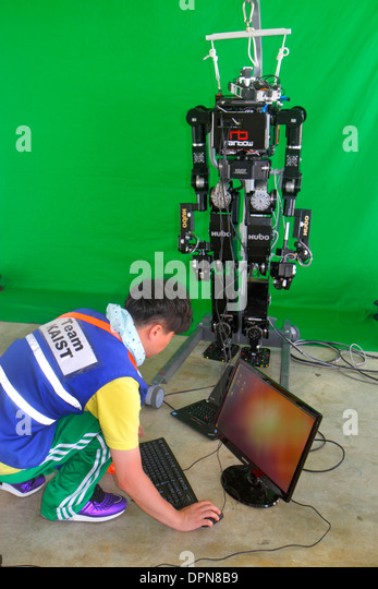 Miami Homestead Florida Speedway DARPA Robotics Challenge Trials remote controlled robot robots man student engineering - Stock Image