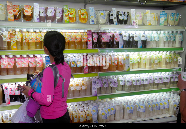 Hong Kong China Island MTR Admiralty Subway Station vendor concession cold drinks sale display Asian woman shopping - Stock Image