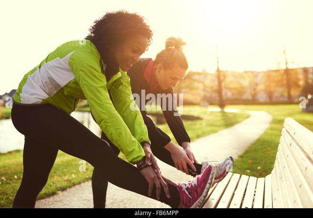 Two girlfriends stretching in sunny park - Stock Image