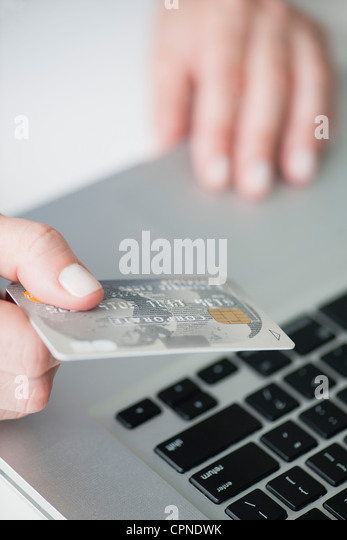 Woman holding credit card above laptop keyboard - Stock Image