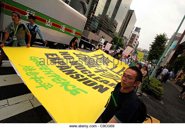 Greenpeace activists carry a large NO NUCLEAR EXPANSION banner down Meji-Dori, Shibuya, during an anti-nuclear protest - Stock Image