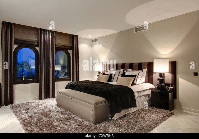 Bed and windows in modern bedroom - Stock Image