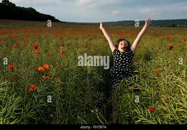 Model released image of a young girl jumping in a poppy field, near Tring, Hertfordshire, UK - Stock Image