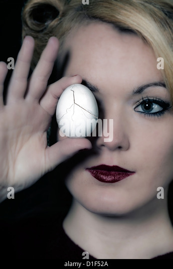 a woman is holding a broken egg in front of her eye - Stock Image