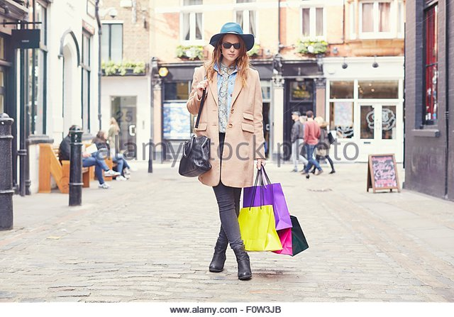Portrait of stylish young woman on shopping spree, London, UK - Stock Image