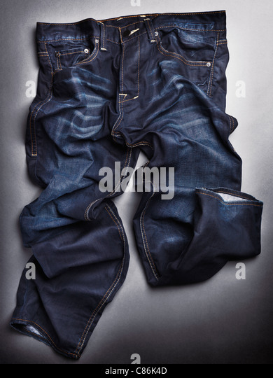 Photo of artistically crumpled blue stone washed mens jeans on gray background - Stock-Bilder