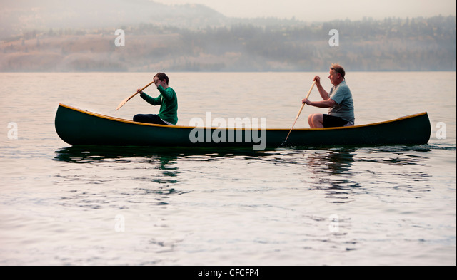 A father and son paddling a canoe at sunset. - Stock Image