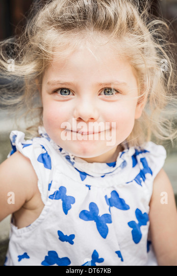 Close up portrait of female toddler in butterfly dress - Stock Image