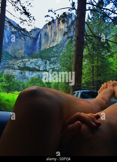 A young adult relaxes with his feet out the car window while gazing up at Yosemite Falls - Stock-Bilder