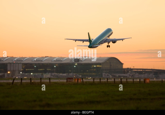 Commercial airplane taking off at London Heathrow Airport with Terminal 5 in the background, UK - Stock Image