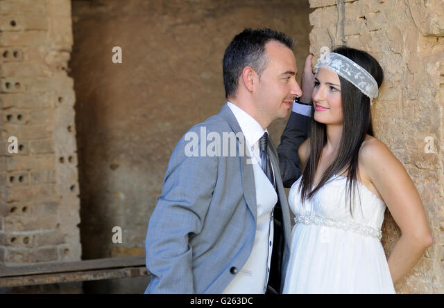 Groom staring at the bride in a warehouse in ruins - Stock Image