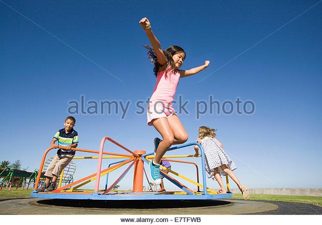 Children jumping off merry-go-round at playground - Stock-Bilder