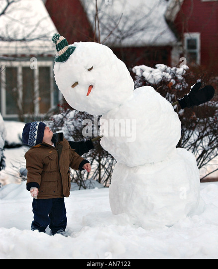 Small boy standing next to a snow man talking - Stock Image