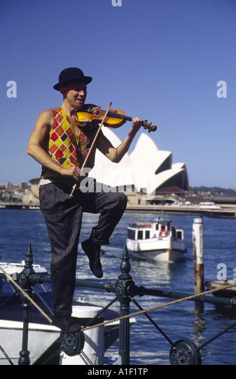 Australia Sydney street artist in front of opera house playing violin - Stock Image