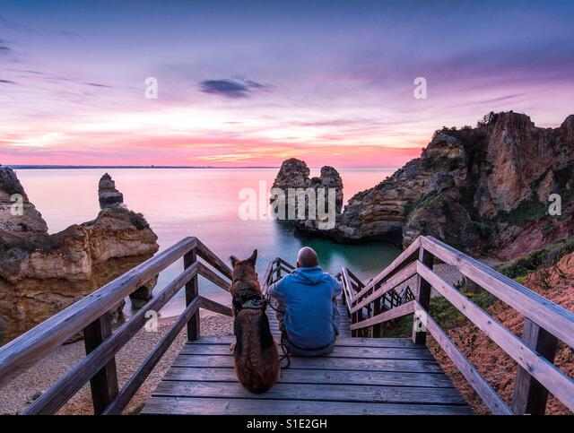 Young man watching beautiful sunrise with belowed dog at praia de camilo in portugal - Stock-Bilder