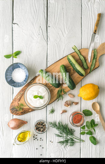 Ingredients for tzatziki preparation on the white  table  vertical - Stock Image