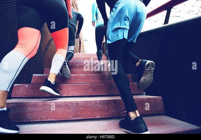 Back view of unrecognizable sportspeople running up stairs. - Stock Image
