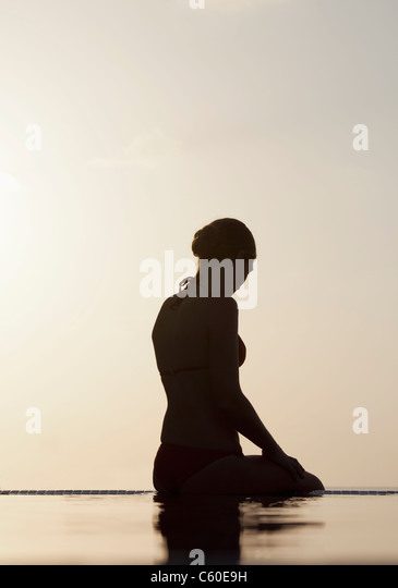 Woman sitting at edge of infinity pool - Stock Image