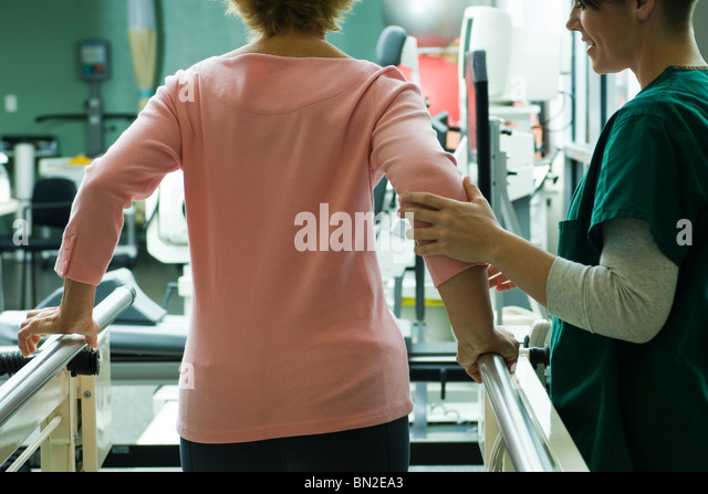 Patient undergoing rehabilitation walking exercises with assistance from physical therapist - Stock Image