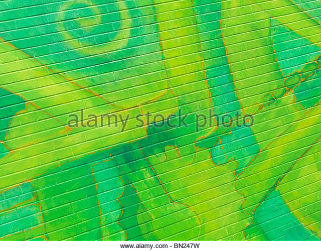 Abstract colorful green mural graffiti on a brick wall - Stock Image