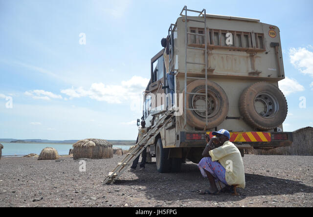 LOIYANGELENI, KENYA - May 18. A man sits in the shade of a tourist track by an El Molo village at Loyangalani by - Stock Image