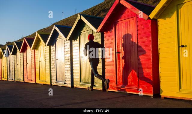Man jogging past beach huts at sunrise. Whitby, North Yorkshire, England. UK - Stock-Bilder