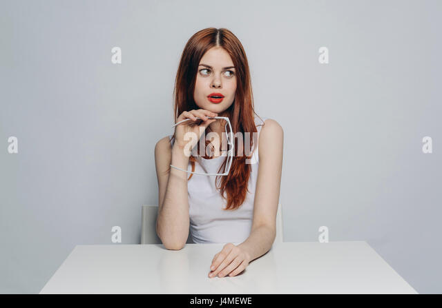 Curious Caucasian woman sitting at table holding white eyeglasses - Stock-Bilder