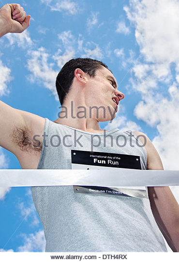 Sportsman Looks Behind To Check Out His Competitors Positions While Finishing The Race In 1st Place - Stock Image