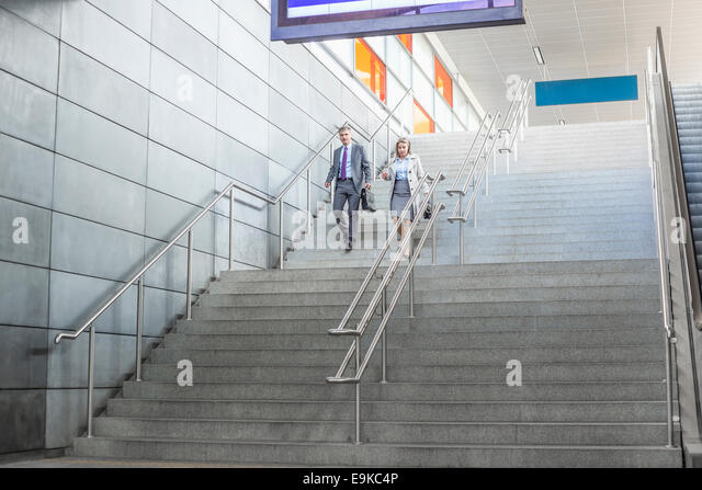 Full length of businessman and businesswoman walk down stairs at railway station - Stock Image