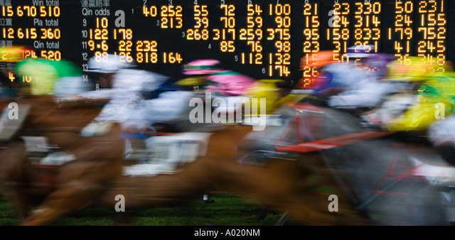 Horses race past large scoreboard during race at Happy Valley racecourse in hong kong - Stock Image