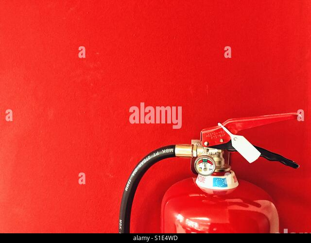 Fire extinguisher detail against a red background - Stock Image