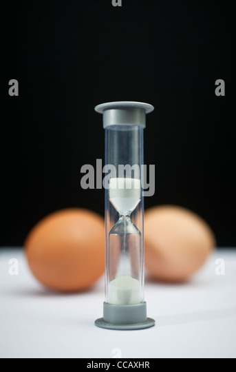 A small egg timer or hourglass, used for timing the boiling of eggs - Stock Image