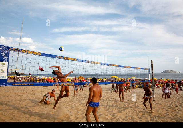 Men playing volleyball on Ipanema beach, Rio de Janeiro, Brazil, South America - Stock Image