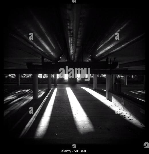 Sunlight slicing through the darkness in an underground carpark - Stock-Bilder