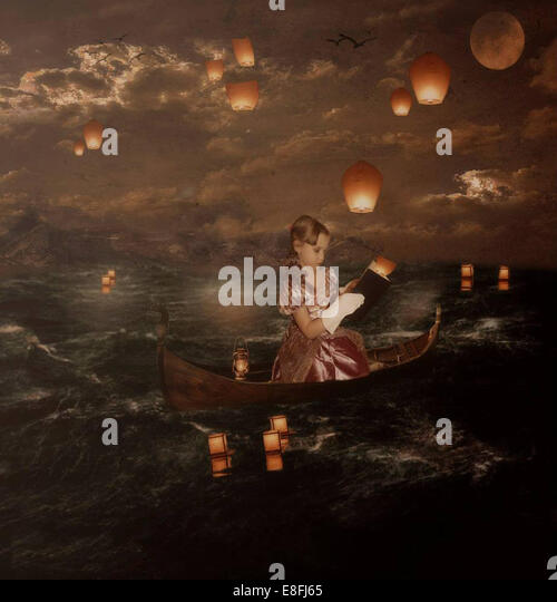 Girl sitting in boat and reading book - Stock Image