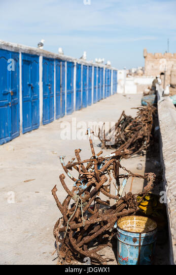 Rusty anchors lie by the side of a path with blue lockers for the fishermen in Essaouira, Morocco - Stock Image