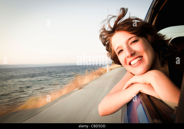 Woman smiling out of car window - Stock Image