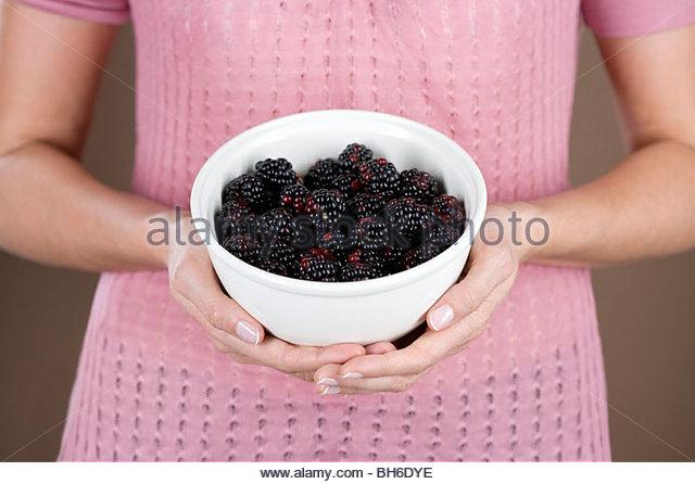 A woman holding a bowl of blackberries - Stock-Bilder